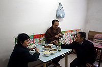 CHINA. Beijing. A migrant worker family eat together Lao San Yu Village (a migrant worker village) in the southern district, Daxing. 2010