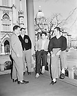 GPHR 45/0042:  A group of four male students sitting on the porch of Sorin Hall with the Basilica of the Sacred Heart and Main Building in the background, c1950s..Image from the University of Notre Dame Archives.