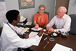 Mature couple consults with physician in his office