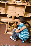 Education preschoool children ages 3-5 block area boy building structure with wooden blocks vertical