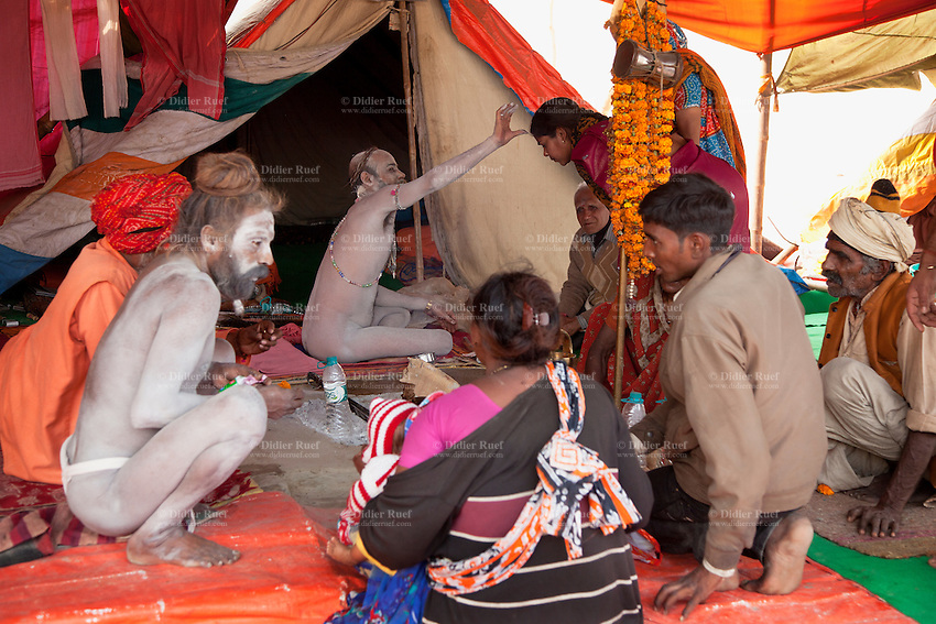 India. Uttar Pradesh state. Allahabad. Maha Kumbh Mela. Two Naga (naked) Sadhu sit on a carpet outside their tent at Sangam. Two couple attend spiritual discourses in front of the tent. One ascetic man puts a tilaka on the front head of a woman. In Hinduism, the tilaka, tika or tilakam or tilak is a mark created by the smearing of powder or paste and worn on the forehead. Tilaka may be worn on a daily basis or for special religious occasions. The Kumbh Mela, believed to be the largest religious gathering is held every 12 years on the banks of the 'Sangam'- the confluence of the holy rivers Ganga, Yamuna and the mythical Saraswati. In Hinduism, Sadhu (good; good man, holy man) denotes an ascetic, wandering monk. Sadhus are sanyasi, or renunciates, who have left behind all material attachments. They are renouncers who have chosen to live a life apart from or on the edges of society in order to focus on their own spiritual practice. The significance of nakedness is that they will not have any worldly ties to material belongings, even something as simple as clothes. A Sadhu is usually referred to as Baba by common people. The Maha (great) Kumbh Mela, which comes after 12 Purna Kumbh Mela, or 144 years, is always held at Allahabad. Uttar Pradesh (abbreviated U.P.) is a state located in northern India. 6.02.13 © 2013 Didier Ruef