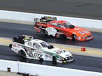 Sep 15, 2013; Charlotte, NC, USA; NHRA funny car driver John Force (near lane) races alongside Johnny Gray during the Carolina Nationals at zMax Dragway. Mandatory Credit: Mark J. Rebilas-