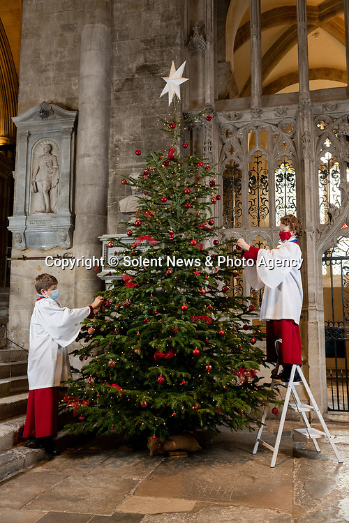 Pictured: Choristers of Winchester Cathedral Choir add the finishing touches to the Tree of Love in the South Transept as Christmas decorations are installed around Winchester Cathedral, which opened for public service to visitors today, December 2nd. <br /> <br /> The tree of love is one of the 4 themed trees in the Cathedral, representing love, hope, faith and memory. <br /> <br /> During the second coronavirus lockdown in England the Cathedral remained open for private prayer and reflection, and after a month-long nationwide lockdown ended today Winchester will enter Tier 2 in the new system implemented by the government to curb the spread of the coronavirus pandemic.<br /> <br /> © Jordan Pettitt/Solent News & Photo Agency<br /> UK +44 (0) 2380 458800