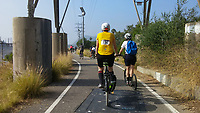 Heading south on the Los Angeles River Greenway Trail from Griffith Park at the start of the 2017 (17th annual) Los Angeles River Ride, the trail loops around one of the large utility poles.  Many bicyclists can be seen ahead of Holland on his kick scooter and Michelle on her Terry Burlington city bike.