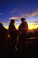 Two women enjoy sunrise on Haleakala at the main visitor center area in Haleakala National Park at a 9,745-ft. elevation.