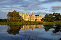 The imposing exterior of Burghley House reflected in the lake