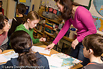 Elementary school Grade 5 female teacher working with student in classroom group working on geography social studies assignment horizontal
