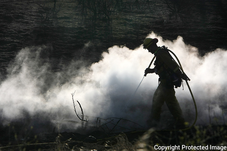 A CAL Fire firefighter douses hotspots of a fire in 2009.  photo for North County Times