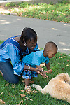 15 month old toddler boy outside with mother interested in pet dog reaching out to pet it, mother talking to him vertical