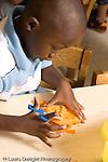 Preschool ages 3-5 art activity play dough boy using scissors on play dough vertical
