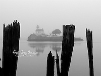 Pomham Rock Lighthouse is shrouded by fog during the early morning.