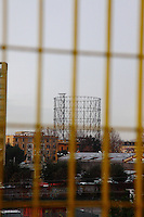 Rome, Garbatella: In a rainy day, an artistic panoramic view  across a yellow grille. The photo is taken from piazza Vallauri (Vallauri square), in the direction of via Ostiense, and the beautiful old gasometer dominates onto the background.