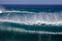 Surfers narrowly escape a big set on the outer reef at Pipeline (off of 'Ehukai Beach Park), North Shore, O'ahu.