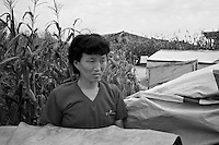 A woman stands near her temporary tarpaulin shelter during a field visit by national and international Red Cross officials to Pongchon county, DPRK on Saturday August 27 2011. Consecutive floods caused by heavy rainfall and strong winds, together with the impact of typhoon Muifa which struck in early August, resulted in the destruction or severe damage of over 9,500 houses, rendering more than 25,000 people homeless between June 23 and August 9, according to data provided by the DPRK government. While flood damage was reported throughout the country, south and north Hwanghae provinces have been worst hit by the repeated flooding, leaving an already vulnerable population in a critical condition.  Photo by Morten Hvaal/Felix Features for IFRC.