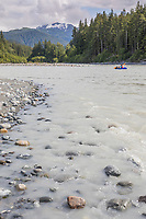 Packrafter crosses Fairweather creek at the Gulf of Alaska, Pacific ocean coast, Glacier Bay National Park, Southeast, Alaska