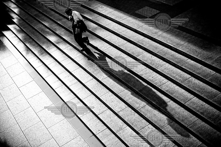 A business walks down steps outside his office in Tokyo.