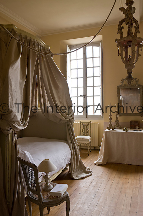 Another bedroom is furnished with a lit a la Polonaise, the bed and dressing table draped in a natural linen