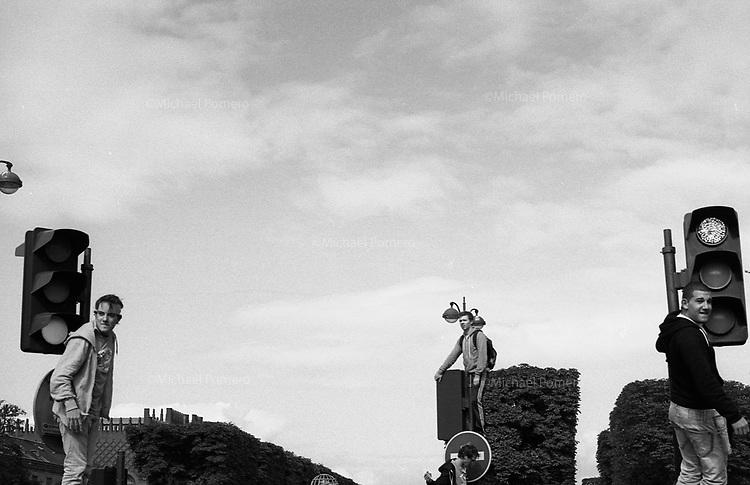 Paris (île de france)<br /> <br /> Trois jeunes hommes debout sur des feux de signalisation en attendant le défilé de la techno parade.<br /> <br /> Three young men standing on the traffic lights waiting for the parade techno parade