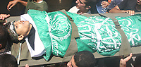 "A Palestinian man carries the body of Hamas militant Mohammed al-Bahtity during his funeral in Gaza August 8, 2007. Israeli troops killed two Palestinian gunmen during a gun battle in the southern Gaza Strip on Wednesday, residents, ambulance workers and army officials said. ""photo by Fady Adwan"""