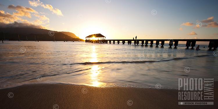 The sun sets through historic Hanalei Pier, Hanalei Bay, Kauai