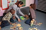 Educaton preschool 4-5 year olds female volunteer student teacher working with children on puzzle activity horizontal
