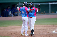 """Tyreque Reed (38) of the Greenville Drive, right, celebrates his home run with Nick Sogard (11) in a game against the Brooklyn Cyclones on Saturday, May 15, 2021, at Fluor Field at the West End in Greenville, South Carolina. Drive players were wearing jerseys for the """"Ranas de Rio de Greenville"""" (Greenville River Frogs), as part of Minor League Baseball's """"Copa de la Diversion"""" program. (Tom Priddy/Four Seam Images)"""