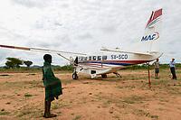 UGANDA, Karamoja, Kaabong, Karimojong boy and Cessna aircraft of MAF Mission Aviation Fellowship, a airline for missionaries, NGO, humanitary aid / MAF Flugzeug auf dem airstrip