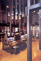 Glasgow School of Art Library with tall ceiling, hanging lights, unique furniture. Designed by Charles Rennie Mackintosh in Art Nouveau style.