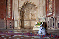 Agra, India.  Taj Mahal Mosque Interior.  Imam Reading from the Koran while Awaiting Prayer Time.  Mihrab (Prayer Niche) indicates the Direction of Mecca.