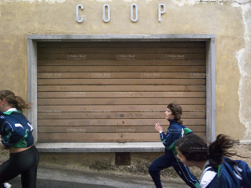 Switzerland. Canton Ticino. Vacallo. Three young girls from the SAM Massagno athletic club are running in front of the closed shutters of the Coop store. Retail business on a sunday afternoon.  21.03.10 © 2010 Didier Ruef