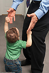 10 monthh old baby boy holding up arms for pickup by father, who is dressed for work