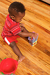 13 month old baby boy sitting on floor playing with cardboard blocks