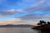 View of a headland on Saddlebag Island with Mount Baker and Cascade Mountains across Padilla Bay in background during sunset, Saddlebag Island Marine State Park, Washington, USA