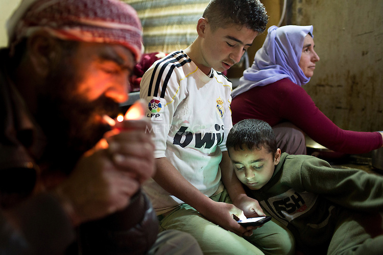 18/02/15 --TANJERO, IRAQ: Saïd lights a cigarette while Ezidiar (9) looks at Serdesht's (13) phone and Ghazal watches television.<br /> <br /> The family of Yezidis, displaced from Sinjar, live next to an oil refinery in the Kurdish Region of Iraq. The young men run the refinery 24 hours a day with little to no safety equipment. Reporting for this article was supported by a grant from the Pulitzer Center on Crisis Reporting