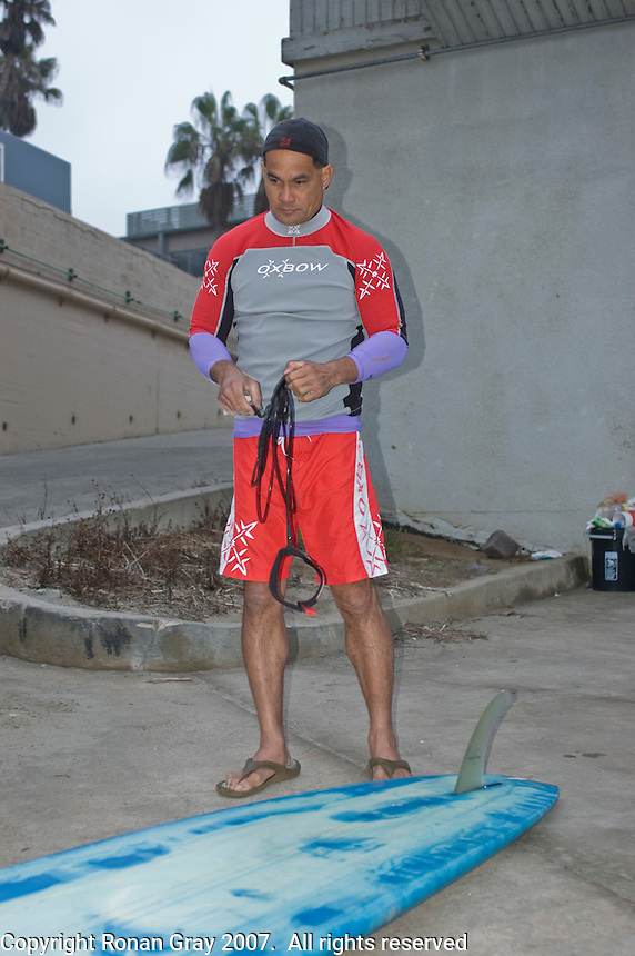 Teddy Casil of Maui prepares his paddleboard before entering the water with Tom Jones at La Jolla Shores, California near Scripps Institution of Oceanography early on Saturday, November 3 2007.  Tom is set to become the first person to paddle the length of the California coast when his journey ends on Sunday at the Mexican border.  He hopes that his achievement will draw attention to the large amount plastic pollution in the oceans.   Tom trained for his endeavor with Laird Hamilton and Teddy on Maui.  Teddy was joining Tom for the last two legs of the trip.