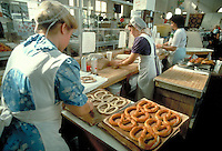 At the farmers market Amish and Mennonite young women prepare soft Auntie Anne pretzels. Amish and Mennonite. Harrisburg Pennsylvania United States Midtown Market.