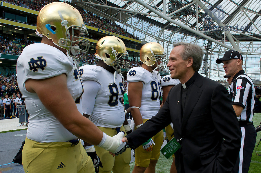 Sept. 1, 2012; Rev. John I. Jenkins, C.S.C., shakes hands with members of the Notre Dame football team prior to the 2012 Emerald Isle Classic against Navy at Aviva Stadium in Dublin, Ireland. Photo by Barbara Johnston/University of Notre Dame
