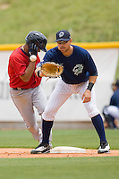 First baseman Josh Kroeger #7 of the Charlotte Knights waits for a throw as Anderson Hernandez #12 of the Columbus Clippers heads back to the bag at Knights Stadium May 25, 2010, in Fort Mill, South Carolina.  Photo by Brian Westerholt / Four Seam Images