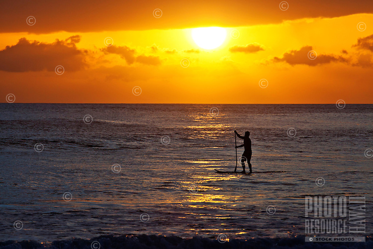 A standup paddler at sunset at Launiupoko Beach Park, Maui.