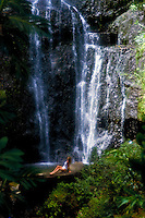Waterfall off road to Hana with woman sitting on rock, Maui