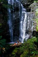 Waterfall off road to Hana with woman sitting on rock, Maui