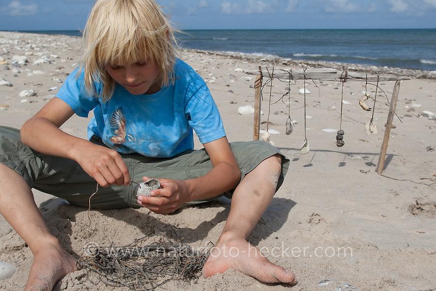 Naturkunst am Strand, Kind bastelt aus Steinen, Muscheln, Schnecken und anderem Strandgut ein Strandmobile, Fundstückemobile, Mobile, eine fadenförmige Alge wird als Schnur verwendet, auf die ein Schneckengehäuse aufgefädelt wird, Strandkunst, Strand, Meer, Küste