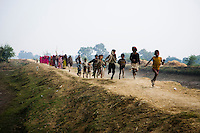 Children run ahead in excitement as members of the 10,000 strong Gulabi Gang march through Banda. In the badlands of Bundelkhand, one of the poorest parts of one of India's most populous states, a gang of female vigilantes have sprung up to fight the oppression of a caste-ridden, feudalistic and male dominated society. In a land where dowry demands and domestic and sexual violence are common, the 'Gulabi Gang' (Pink Gang), so called for their uniform of shocking pink saris, are picking up their lathis (traditional Indian sticks) to fight against corruption and violence against women.