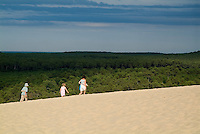 Mother and her two children walking on the Great Dune of Pyla, Aquitaine, France.