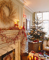 Beaded garlands and wreaths hang from and above the fireplace while instead of curtains the window is covered by a row of crystal drops