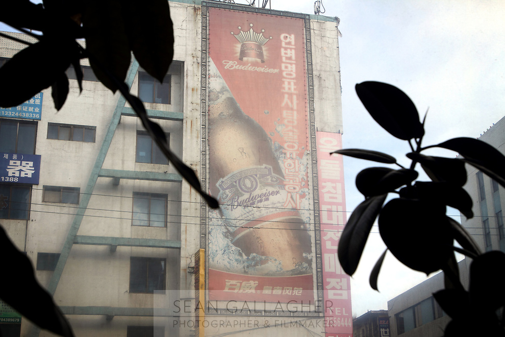 China. Jilin Province. A Budweiser advertisement in the town of Yanji, close to the border with North Korea. The town is part of the Korean Autonomous Prefecture in the north-east of the country, hence many signs are in both Chinese and Korean. 2011