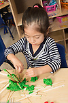 Education Preschool 3-4 year olds girl working on play dough and tongue depressor construction art activity