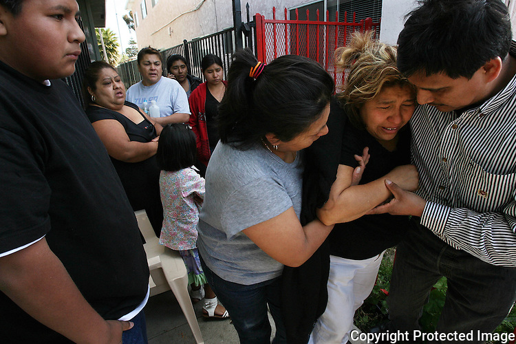 """Maria Perez, mother of shooting victim Antonio Carachurit, 17, is assisted leaving the scene of the shooting in Oceanside, California, in March, 2012. """"She has been crying all night,"""" said one of the victim's cousins.  for the North County Times."""