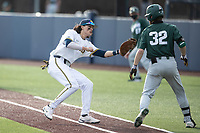 Michigan Wolverines first baseman Jake Marti (7) tags Michigan State baserunner Zach Iverson (32) on March 22, 2021 in NCAA baseball action at Ray Fisher Stadium in Ann Arbor, Michigan. Michigan State beat the Wolverines 3-0. (Andrew Woolley/Four Seam Images)