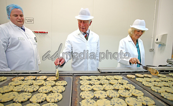 07 July 2015 - Wrexham, Wales - Camilla, Duchess of Cornwall and Prince Charles, Prince of Wales flipping Welsh Cakes on hot plates during their tour of Village Bakery in Wrexham as they continue their tour of Wales. Photo Credit: Alpha Press/AdMedia